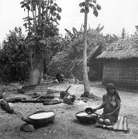 Женщина перемешивает напиток из маниока