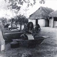 Женщина разбавляет пережёванное тесто из маниока водой